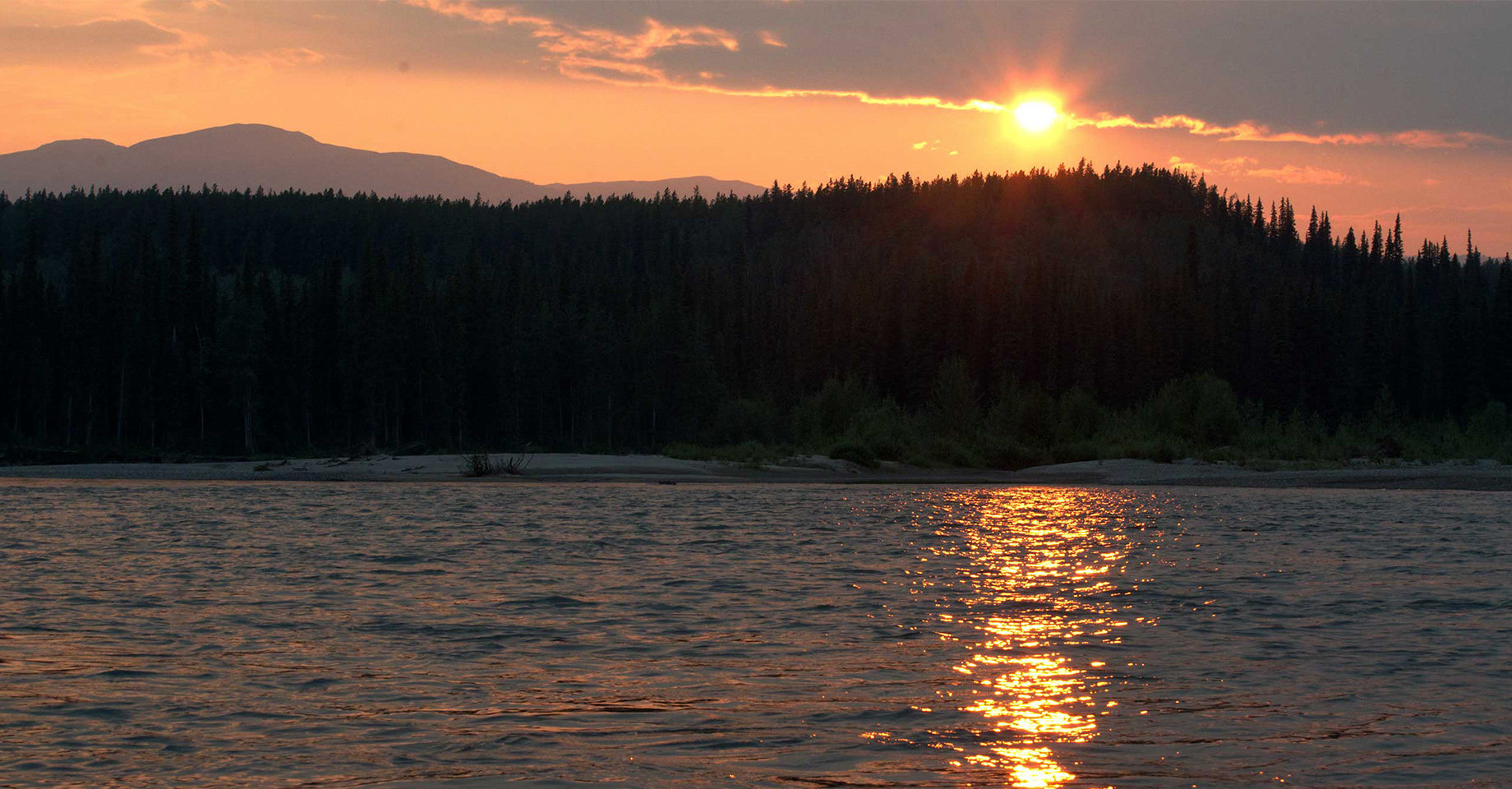 The Midnight Sun, almost setting over a lake in the Yukon.