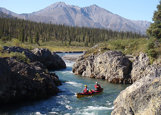 Couple canoeing down a Northwest Territory river.